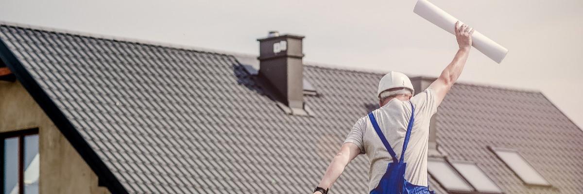 Mann mit Bauplan springt in die Höhe