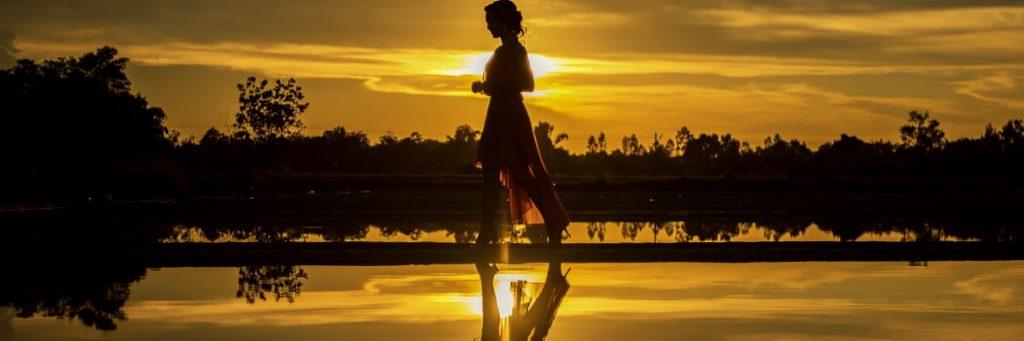 Frau geht durch Wasser mit Spiegelbild