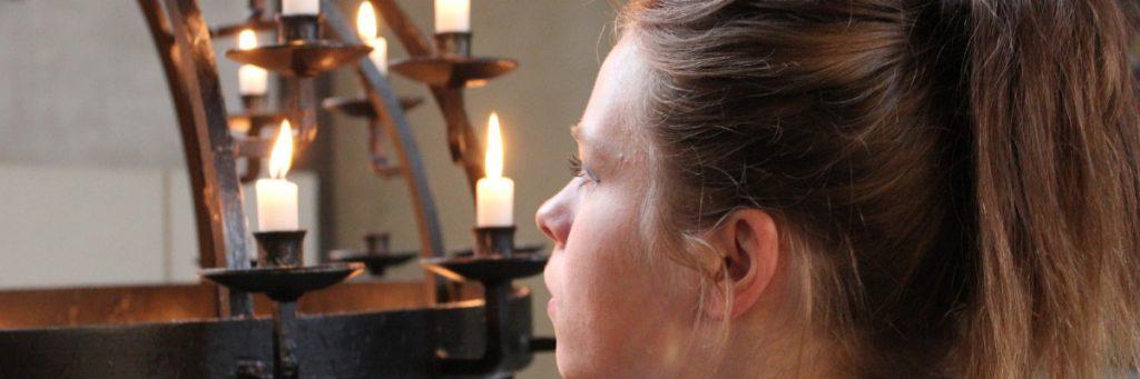 Frau vor einem Kerzenständer